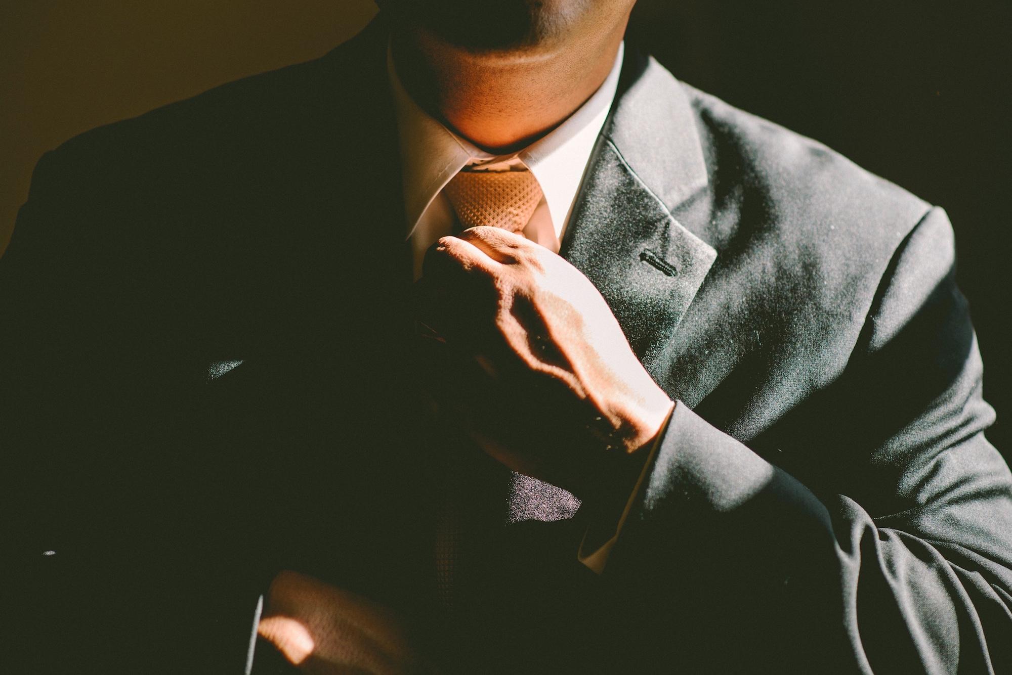 Man in suit straightening neck tie